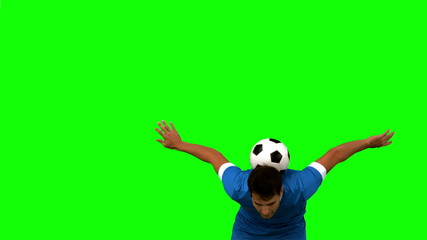 Man juggling a football with head on green screen