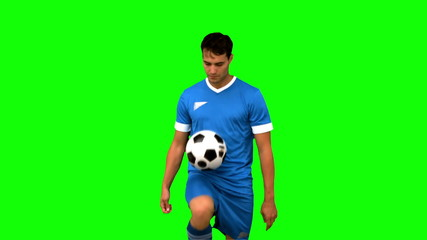 Man juggling a football with his knee on green screen