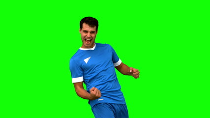 Cheerful football player gesturing on green screen