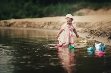 little girl plays with paper boats in river