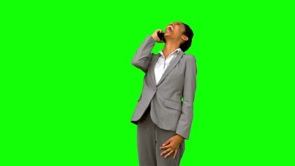 Happy businesswoman laughing while phoning on green screen
