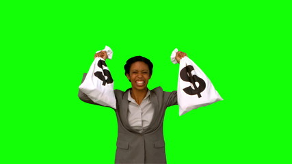 Businesswoman holding money bags on green screen