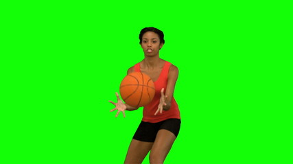 Pretty woman catching and throwing a basketball on green screen