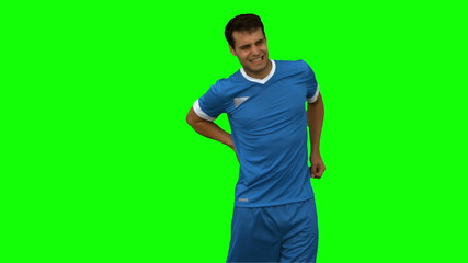 Football player suffering from back pain on green screen
