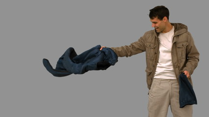 Man rolling out his sleeping bag on grey screen