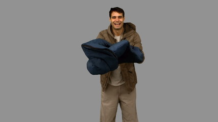Cheerful man rolling out his sleeping bag on grey screen