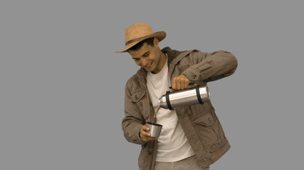 Man pouring coffee from a vacuum flask on grey screen