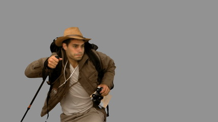 Man orienteering while holding a hiking stick on grey screen