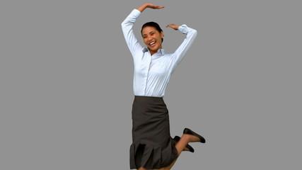 Happy businesswoman raising arms on grey screen