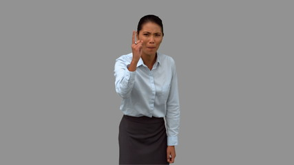Angry businesswoman pointing on grey screen