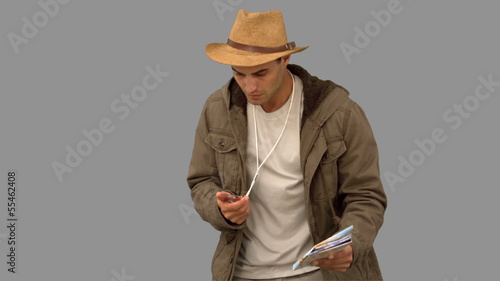 Man orienteering with a map and a compass on grey screen