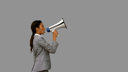 Businesswoman shouting into a megaphone on grey screen
