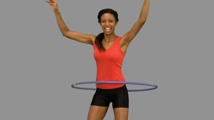 Woman playing with a hula hoop on grey screen