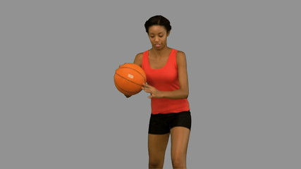 Woman catching and throwing a basketball on grey screen