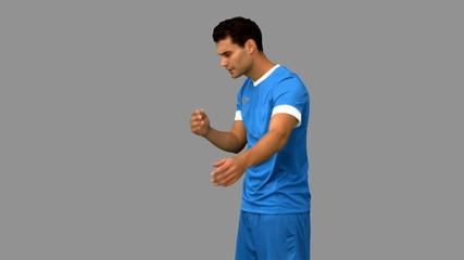 Sad football player holding his head on grey screen