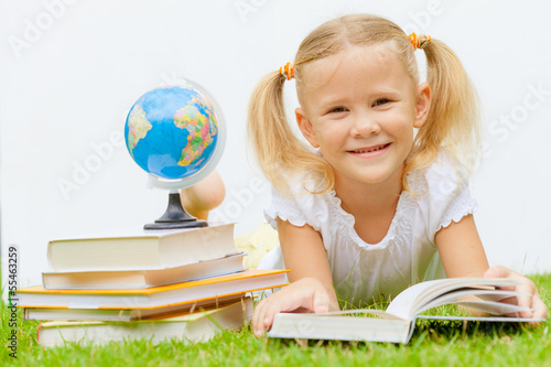 little girl with books lying on the grass