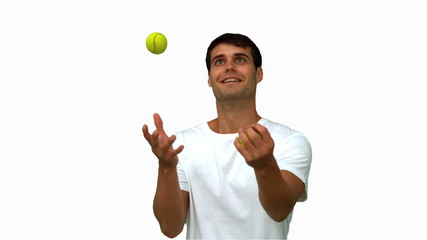 Man dribbling with tennis balls on white screen