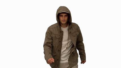 Man with a coat walking toward camera on white screen