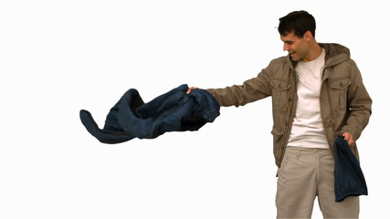 Man rolling out his sleeping bag on white screen