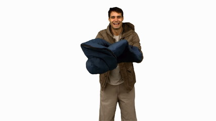 Cheerful man rolling out his sleeping bag on white screen