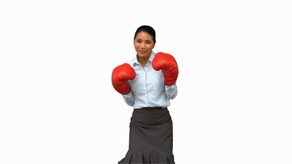 Businesswoman with boxing gloves hitting on white screen