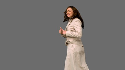 Businesswoman jumping and giving thumbs up on grey screen