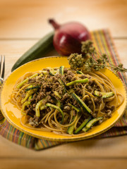 spaghetti with ragout and zucchinis, selective focus