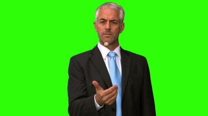 Elegant businessman throwing a coin in the air on green screen