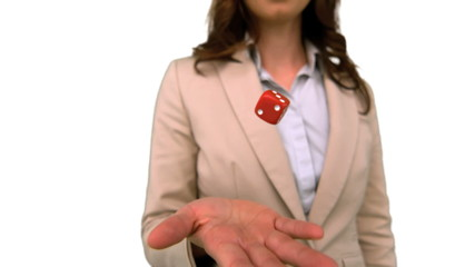 Businesswoman throwing a die on white screen in slow motion