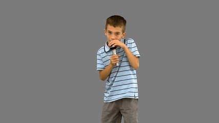 Little boy holding a microphone and singing on grey screen