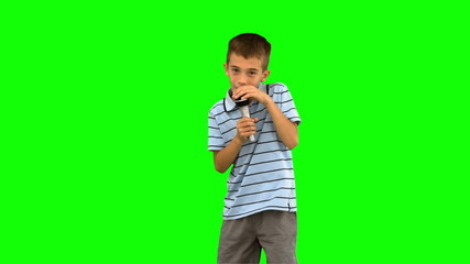 Little boy holding a microphone and singing on green screen