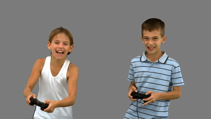 Siblings playing video games on grey screen