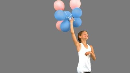 Little girl playing with balloons on grey screen