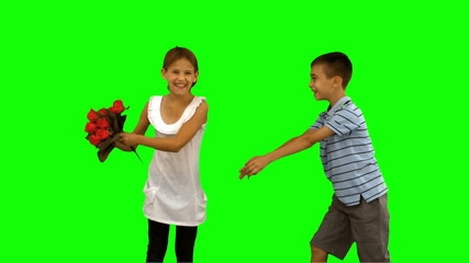 Boy offering flowers to a little girl on green screen