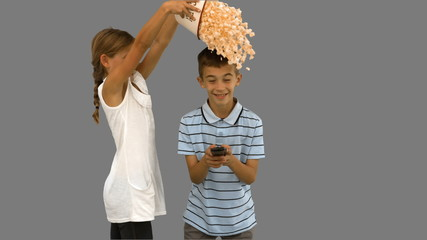 Sister pouring popcorn on brothers head on grey screen