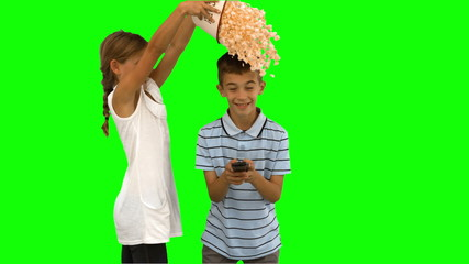 Sister pouring popcorn on brothers head on green screen