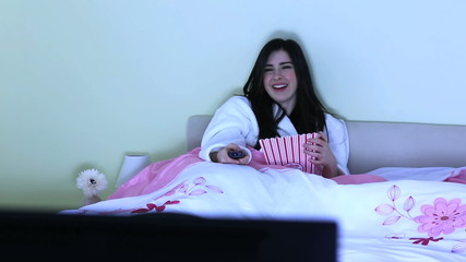 Cheerful young woman watching television