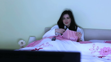 Young woman watching horror movie