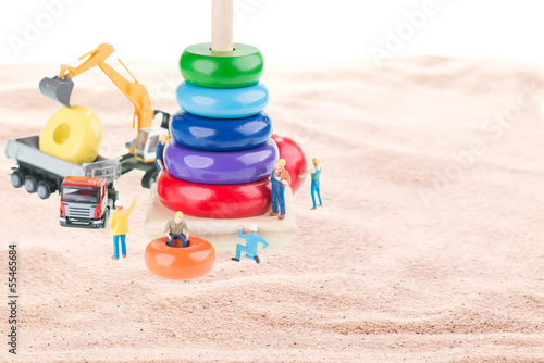 Construction site with miniature workers, dump truck, excavator