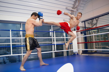 Men kickboxing. Two confident men kickboxing on the ring