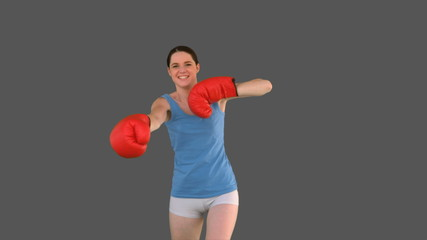 Pretty young model with boxing gloves punching