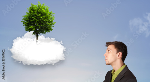 Young man pointing at a green tree on top of a white cloud