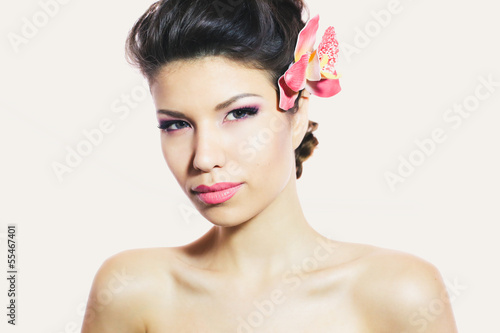 Amazing beauty with ideal make-up and hair with pink flower