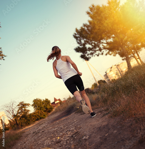 Fitness female runner working out on the nature.