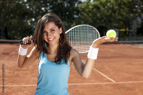 Young girl holding tennis ball on court
