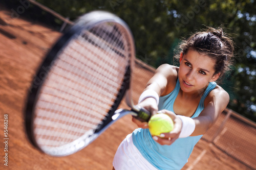 Young girl catching a ball in tennis court