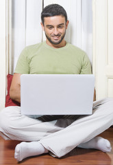 Happy Young Man Working on Laptop at Home