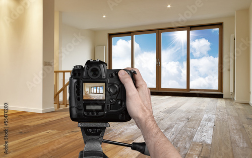 Leinwanddruck Bild Man photographing empty living room with digital camera