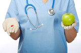 Young doctor with pill and apple