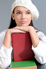 Beautiful student with books thinking.Girl wearing a beret.